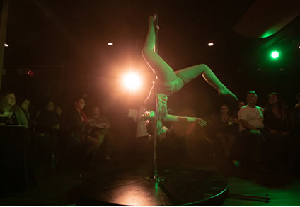 image-of-flying-curves-dance-studio-pole-dance-performer-inverted-on-pole